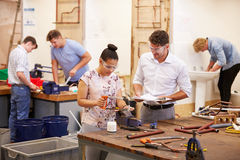 Professeur Helping College Students étudiant la tuyauterie photo stock