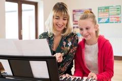 Professeur Helping Female Student pour jouer le piano dans la leçon de musique photos libres de droits