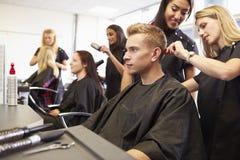 Professeur Helping Students Training à devenir coiffeurs photos stock