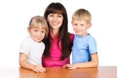 Professeur heureux s'asseyant à la table avec deux enfants images libres de droits