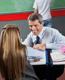 Professeur heureux Teaching Little Girl au bureau Images stock