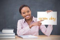 Professeur heureux tenant la page montrant la journée 'portes ouvertes' Photographie stock