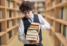 Professeur humoristique de ballot avec beaucoup de livres dans la bibliothèque images libres de droits