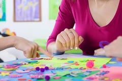 Professeur jouant des puzzles colorés avec des enfants Photo stock