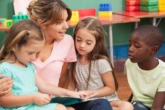 Professeur lisant un livre à sa classe de jardin d'enfants Photos stock