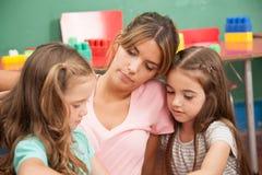 Professeur lisant un livre à sa classe de jardin d'enfants Images libres de droits