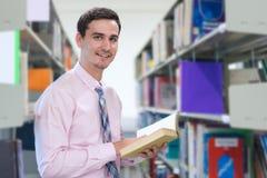 Professeur lisant un livre pour apprendre dans la bibliothèque photos libres de droits
