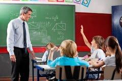 Professeur Looking At Schoolboy soulevant la main Photographie stock libre de droits