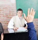 Professeur Looking At Student soulevant la main dedans Image libre de droits
