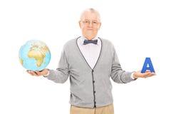 Professeur mûr de géographie tenant un globe Photographie stock libre de droits