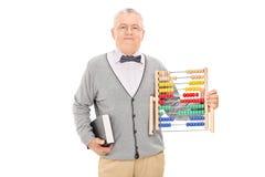 Professeur mûr tenant un livre et un abaque Photos stock