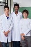 Professeur With Male Students se tenant ensemble dedans Photo stock