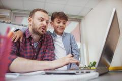 Professeur masculin amical aidant son petit étudiant image stock