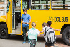 Professeur mettant à jour la liste de contrôle d'enfants tout en entrant dans l'autobus Photo stock