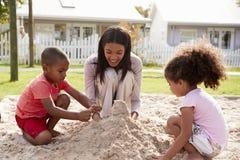 Professeur At Montessori School jouant avec des enfants dans le puits de sable Photographie stock