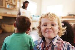 Professeur At Montessori School lisant aux enfants au temps d'histoire Photo stock