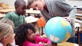 Professeur montrant un globe à ses élèves banque de vidéos
