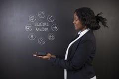 Professeur ou étudiant sud-africain ou d'Afro-américain de femme tenant le media de social de comprimé images stock