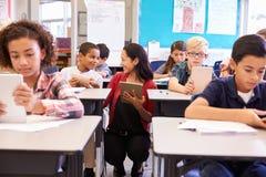 Professeur parmi des enfants avec des ordinateurs dans la classe d'école primaire images libres de droits