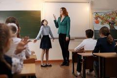 Professeur plus âgé de sourire près du tableau demandant à l'étudiant à la leçon de maths images stock