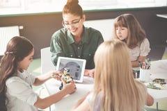 Professeur positif et enfants créant le jouet Photo stock