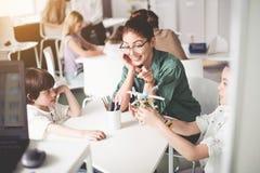 Professeur positif et enfants observant au jouet Photographie stock libre de droits