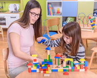 Professeur préscolaire Helps Cute Girl pour construire Toy Castle Photos libres de droits