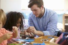 Professeur And Pupils Working aux Tableaux à l'école de Montessori photos stock