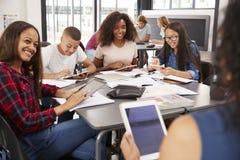 Professeur s'asseyant avec des étudiants de lycée à l'aide des comprimés Photographie stock