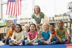 Professeur s'asseyant avec des enfants dans la bibliothèque