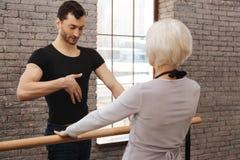 Professeur sûr de danse instruisant la femme agée dans le studio de danse Photos stock