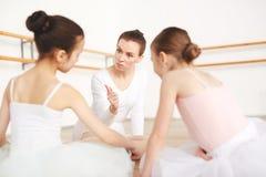 Professeur strict à l'école de danse parlant avec des étudiants images stock
