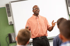 Professeur Talking To Class se tenant en Front Of Whiteboard Photo stock