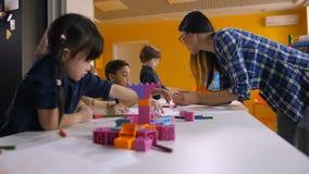 Professeur travaillant avec les enfants créatifs dans le jardin d'enfants banque de vidéos