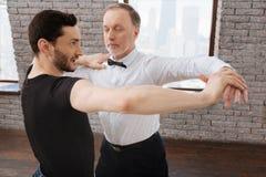 Professeur utile de danse tangoing avec l'homme âgé à la salle de bal Image libre de droits