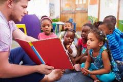 Professeur volontaire lisant à une classe des enfants préscolaires image stock