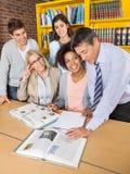Professeurs et étudiants discutant au-dessus du livre dedans Images stock