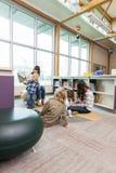 Professeurs et étudiants primaires dans la bibliothèque Image stock