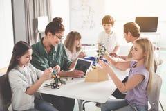 Professeurs positifs et enfants créant des robots Images libres de droits