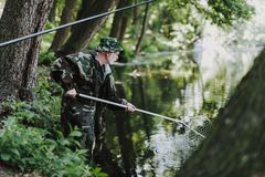 Professional aged angler using fishing nets in the river. Professiaonal elderly fisherman holding nets while fishing on the weekend royalty free stock photo