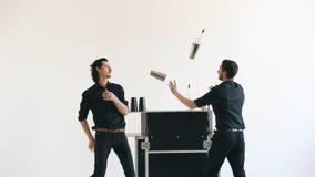 Professinal玩杂耍瓶和震动鸡尾酒的侍酒者人在白色背景演播室的流动酒吧桌上户内 图库摄影