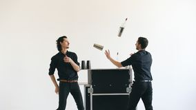 Professinal bartender men juggling bottles and shaking cocktail at mobile bar table on white background studio indoors. Professinal bartender men juggling Stock Photography