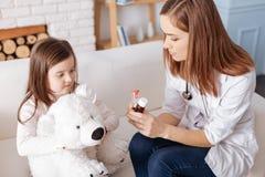 Professioanal doktor som ordinerar preventivpillerar för liten flicka Arkivfoto