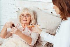 Professioanl doktor som hemma vising den sjuka äldre kvinnan fotografering för bildbyråer