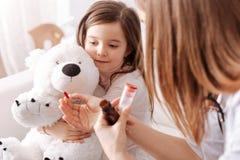 Professioanl doktor som lite ger preventivpillerar till flickan royaltyfria bilder