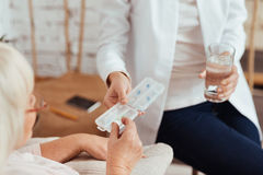 Professioanl nurse giving pills to elderly woman Royalty Free Stock Image