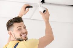 Technician installing CCTV camera on ceiling indoors. Professioanl technician installing CCTV camera on ceiling indoors Royalty Free Stock Image