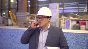 Profession, business and telecommunications, architect talking on cell phone on the background of the pool under. Profession, business and telecommunications stock video footage