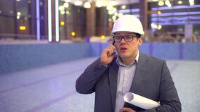 Profession, business and telecommunications, architect talking on cell phone on the background of the pool under. Profession, business and telecommunications stock footage