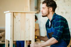 Carpenter testing wood plank evenness at workshop. Profession, carpentry, woodwork and people concept - young carpenter testing wood plank evenness at workshop Royalty Free Stock Photos